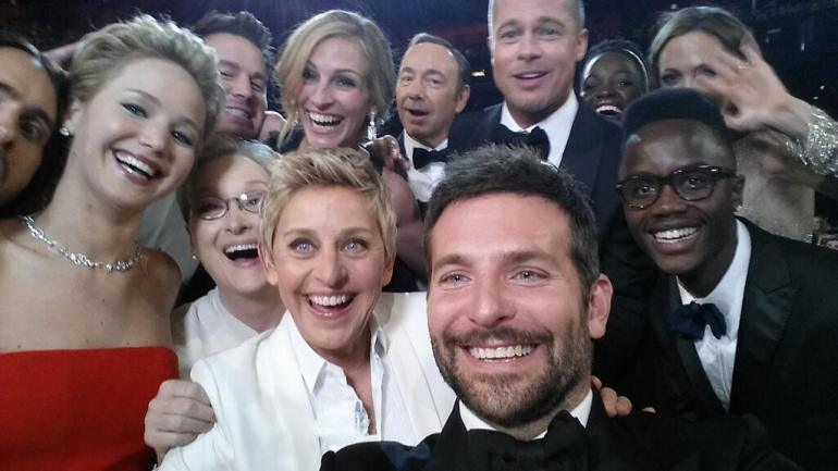 Ellen pulls celebrities from the crowd to take a selfie on twitter and breaks the record for most retweets.