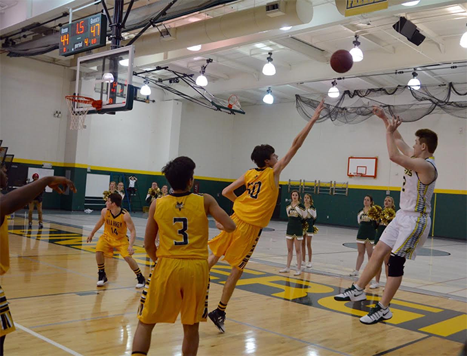 Ryan Lacefield (12) shoots the game tying three pointer at the end of the second half in the Vianney game. Later, in overtime, Lacefield made another last second shot to win the game.