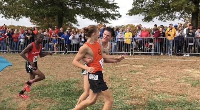 Connor Kingsland (12) helps fellow runner across the finish line.